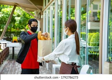 Camarera sostiene una bolsa de papel para el pan y lo envían a los clientes. Quita el pedido. Los tailandeses toman comida del restaurante.