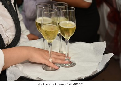Waitress holding a dish of champagne and wine glasses at some festive event,