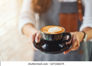 A waitress holding and serving a cup of hot coffee in cafe