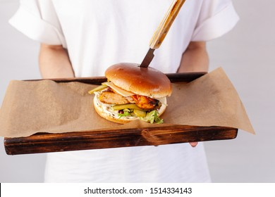 Waitress is holding a tray with hot chicken burger indoors