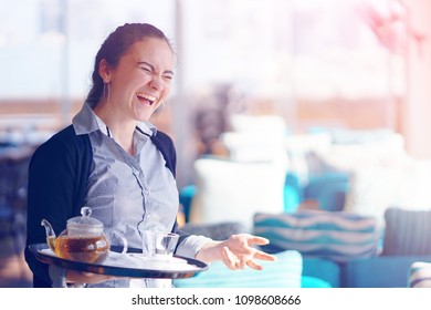 Waitress laughs. The waitress is carrying tea. Hospitable girl waitress holding tray with cup of tea and tea glass teapot for the client at the hotel restaurant. The concept of service.