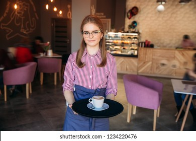 Waitress offering a cup of coffee in cafe. cappuchino