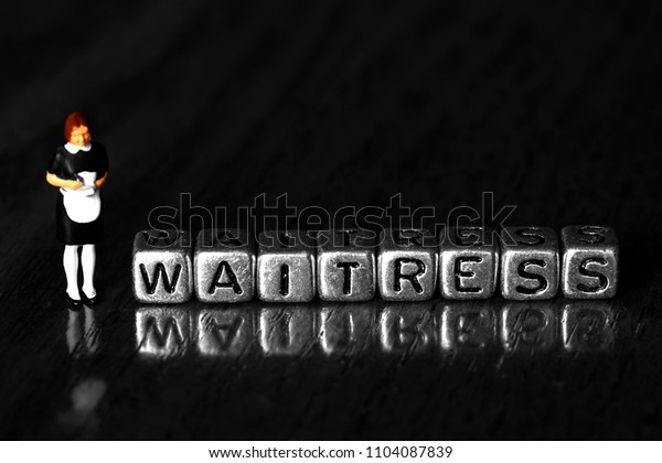 Waitress on beads with a scale model waiter standing next to word on wooden background