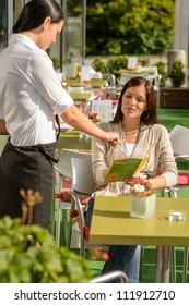 Waitress point menu woman in cafe bar terrace order food