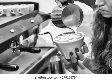 Waitress pouring milk making cappuccino