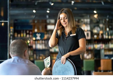The waitress refuses to receive a tip from the client in the hotel bar. The girl is frustrated. The girl is upset and outraged by the rudeness of the client. Emotions. The concept of service.