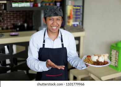 waitress restaurant asian man holding rise or nasi lemak. asian man smiling waitress holding plate of meal in a restaurant. yogyakarta indonesia. may 31, 2018