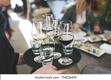 waitress at restaurant serving red and white wine