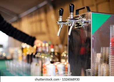 Waitress serves alcoholic drinks under a tent with a table full of alcoholic beverages and bottles with a beer faucet machine