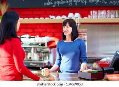 waitress serves customer in coffee shop