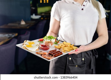 Waitress serving breakfast at a restaurant, Mediterranean breakfast on a tray in the hands of a waitress in a cafe