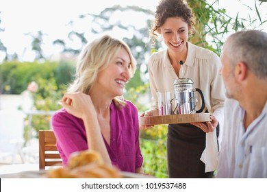 Waitress serving coffee to couple