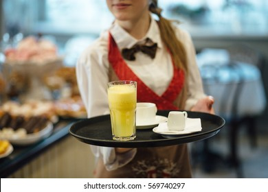 Waitress serving  coffee, milk and  orange juice.
