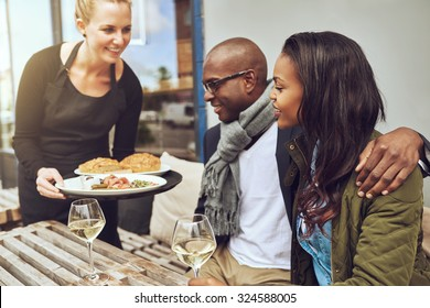 Waitress serving food to an affectionate African American couple sitting arm in arm at a restaurant table