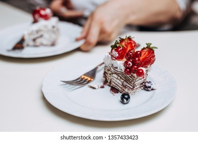 Waitress serving a piece of delicious  cherry cake with white cream on a white plate in a restaurant. The cake is covered with fresh strawberries, red currant and black currant.
