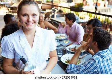 Waitress Serving Tables At Outdoor Restaurant