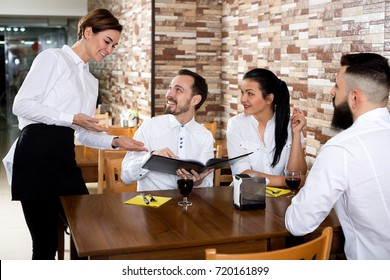 Waitress taking order at table of people having dinner together