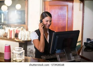 Waitress talking on phone at restaurant counter