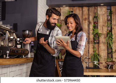 Waitress using a tablet computer and waiter with coffee machine in the bar