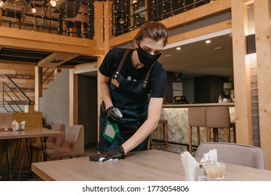 A waitress who wears a black medical face mask and disposable medical gloves is holding a bottle with sanitizer and cleaning a table with a rag in a restaurant. A barista is waiting for clients.