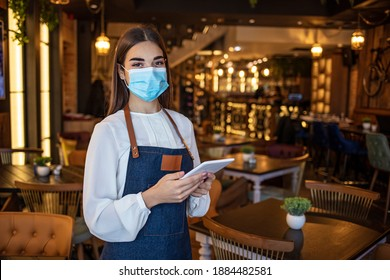 Waitress working on touchpad while wearing protective face mask. Beautiful waitress working at a restaurant wearing a facemask. Waitress wearing a facemask and using a tablet computer