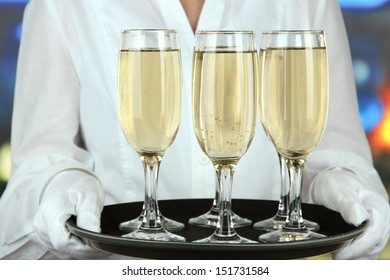Waitresses holding tray with glasses of champagne