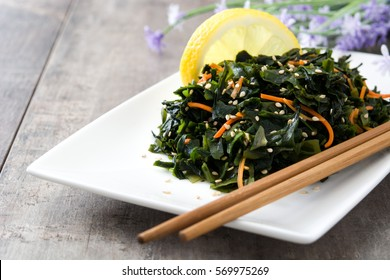 Wakame salad with carrot, sesame seeds and lemon juice in plate on wooden table