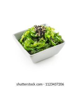 Wakame salad with seaweed and sesame seeds isolated on white.