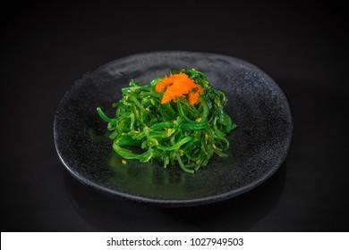 Wakame Sashimi, wakame on traditional ceramic dish, Japanese food style, Japanese menu, wakame seaweed salad toped with shrimp eggs on black background, selective focus