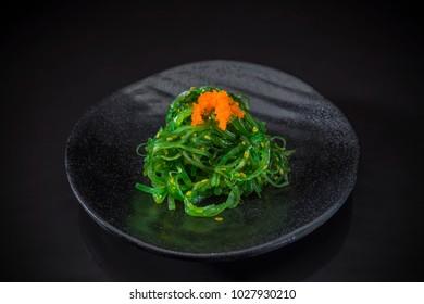 Wakame Sashimi, wakame salad served on traditional Japanese food on ceramic dish, Japanese food style, Japanese menu, wakame seaweed salad toped with shrimp eggs on black background, selective focus
