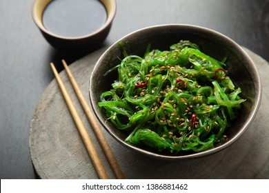 Wakame seaweed salad with sesame seeds and chili pepper in a bowl on a wooden slice