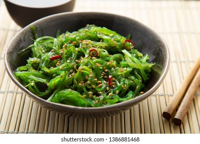 Wakame seaweed salad with sesame seeds and chili pepper in a bowl on a bamboo mat