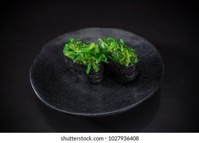 Wakame Sushi Nigiri, Sushi wakame served on traditional Japanese food on ceramic dish, Japanese food style, Japanese menu, sushi wakame, seaweed sushi on black background, selective focus