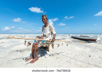 Wakatobi, Indonesia:Nov 10, 2017:Unidentified old man of  Buton Ethnic holding a dried fish and poses for camera in the Werake village Hoga Island located in Wakatobi, South East Sulawesi, Indonesia.