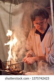 Wakayama / Japan - March 29th 2018: Man grilling meat, street food stall at Wakayama city festival, Japan
