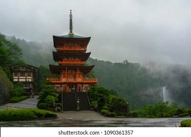 Wakayama , Japan - May 8 , 2018 : Three-story Sanjudo pagoda of Seiganto-ji temple with Nachi falls in the rain , listed as a UNESCO World Heritage Site in Wakayama Prefecture