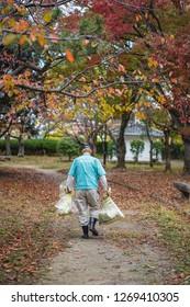 Wakayama - Nov. 17, 2018: Japanese worker is seen carrying garbage in a park near Wakayama Castle