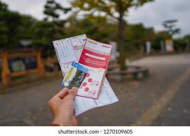 Wakayama - Nov. 17,18: Tourist holding city map and bus card for travelling in Wakayama