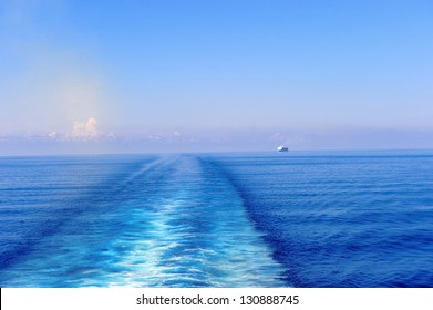 The wake behind a cruise ship with another cruise ship in the distance