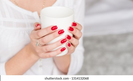 Wake up beverage. Woman manicured hands with white cup of hot morning drink.