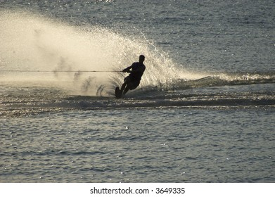Wake boarder kicking up spray during summer evening