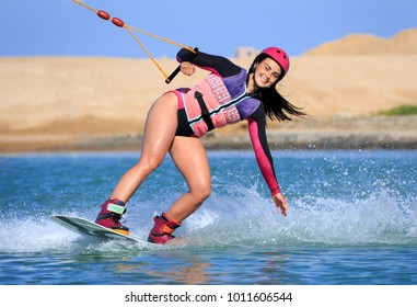 Wake boarding female sportsman girl jumping high wake boarding raley trick with huge water splash in the cable park, active sports, life style, recreation hobby fun, rider woman on the air background