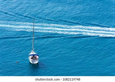 wake of a boat near an anchored sailboat