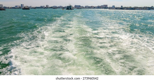 The wake of a boat as seen from the stern of a ship at coast of Pattaya city.