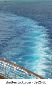 Wake from a cruise ship in the Bahama's bright aqua water.  This was taken from the upper deck with only water and the ship's rail visible.