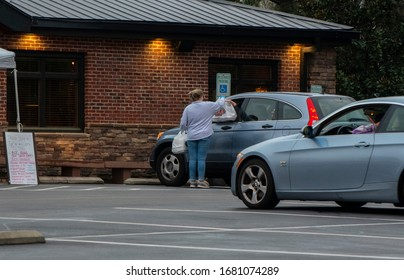 Wake Forest, NC/United States- 03/23/2020: A restaurant employee delivers takeout orders to customers in their cars. In restaurant dining was banned by executive order amid the coronavirus epidemic.