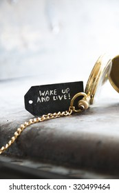 """""""wake up and live""""  inscription on the label and gold pocket watch"""