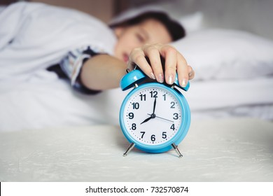 Wake up in the morning, Defocus Woman sleep on bedroom, Time 8 o clock am, sleepy and lazy dont want getting out of bed. Girl catch and stop snooze alarm by hand
