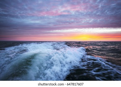 A wake of a motorboat at sunset time