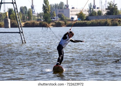 Wake Park. Summer beach water sports. Athlete glides on water on board. Kite on water. Kiteboarding, Wakeboarding. Athlete in water suit on blackboard. Summer sports background